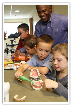 doctor and kids working with teeth models